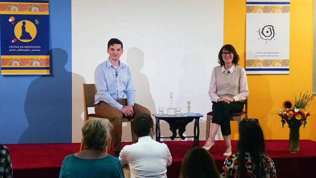 Mathieu Brégégère à gauche et Marie-Laurence Cattoire sont assis sur une estrade face à un public de méditants. Ils regardent tous deux la caméra en souriant avant de démarrer la conférence sur les adolescents.