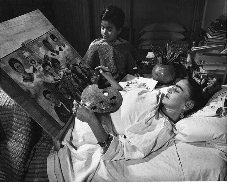 Une photo noir et blanc montre Frida Kahlo allongée dans son lit en train de peindre. Un jeune garçon la regarde
